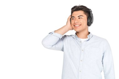 cheerful asian man listening music in headphones, smiling and looking away isolated on white