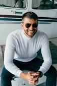 mosolygó ember napszemüveget ült összeszedve kézzel sík közelében