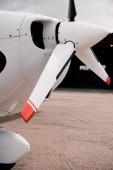 Fotografie weißes Flugzeug mit großem Propeller am Boden unter dem Himmel