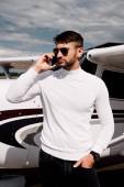 Bärtiger Mann mit Sonnenbrille spricht in Flugzeugnähe auf Smartphone