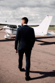 Photo back view of businessman in formal wear walking near plane