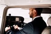 Fotografie pilot ve formálním opotřebení sedícího v letadle a v hospodářství