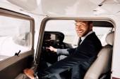 Fényképek mosolygós pilóta formális kopási ül a síkban és a gazdaság