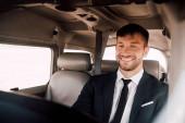 Photo smiling bearded pilot in formal wear sitting in plane