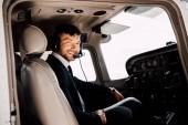 Fotografie lächelnde bärtige Pilot in formeller Kleidung sitzen dim Flugzeug
