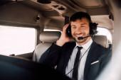 usměvavý vousatý pilot ve formálním oblečení a náhlavní soupravě sedící v letadle