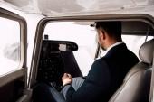 Fotografie Geschäftsmann in offizieller Kleidung sitzt im Flugzeug und hält Ordner in der Hand