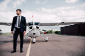 Photo full length view of businessman in formal wear holding laptop near plane in sunny day