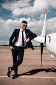 full length view of smiling businessman in formal wear standing with hand in pocket near plane