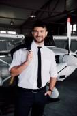 Lächelnder Pilot in offizieller Kleidung, der neben dem Flugzeug steht und in die Kamera blickt