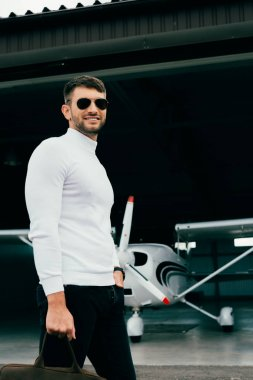 Smiling stylish man in sunglasses standing near plane stock vector