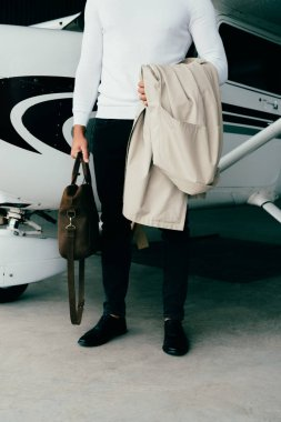 Partial view of young man holding coat and bag while standing near plane stock vector