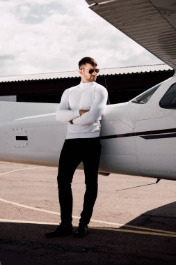 Full length view of serious man in sunglasses standing with crossed arms near plane stock vector