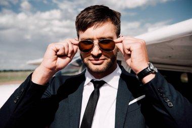Confident businessman in formal wear standing near plane stock vector