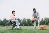 jóképű ember készül helyet a piknik közelében fogyatékos barátnője a parkban