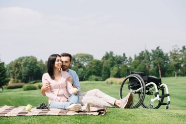 happy handsome man hugging young disabled girlfriend while sitting on blanket in park