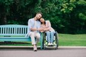 Fotografie schöne behinderte Frau mit glücklichem Freund, der zusammen im Park ruht