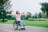 Glückliche behinderte Frau im Rollstuhl gestikuliert beim Blick in den klaren Himmel