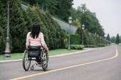 Fotografie Rückansicht junger behinderter Frauen, die im Rollstuhl im Park spazieren gehen