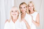 šťastné elegantní třígenerační blondýny v celkem bílých oblečcích