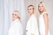 Fényképek oldalnézetből mosolyogva elegáns három generációs szőke nő összesen fehér ruhák nézett kamera