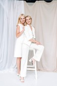 smiling elegant blonde mature mother gently hugging young daughter on chair