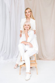 full length view of elegant blonde grandmother and granddaughter together in total white outfits
