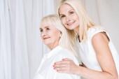 elegantní blonďatá dcera, která objímá starší matku