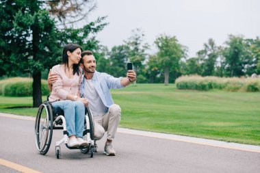 Happy man hugging disabled girlfriend and taking selfie on smartphone in park stock vector