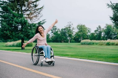 happy disabled woman gesturing and looking at camera while sitting in wheelchair in park