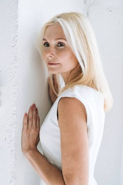 Dreamy blonde mature woman near white wall stock vector