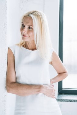 Smiling blonde mature woman near white wall and window looking away stock vector