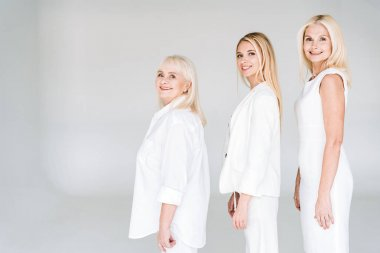 side view of three generation blonde women looking at camera isolated on grey