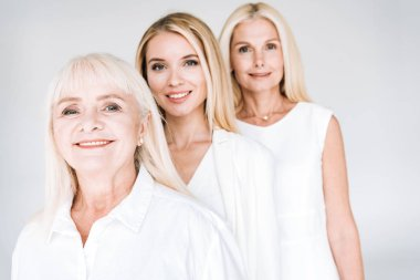 selective focus of attractive three generation blonde women isolated on grey
