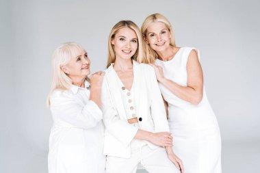 three generation blonde women smiling isolated on grey