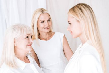 Elegant three-generation blonde women in total white outfits looking at each other stock vector