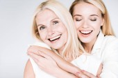 happy blonde mature mother and young daughter in total white clothes embracing isolated on grey