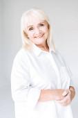 boldog szőke Senior nő, fehér ruhában izolált szürke