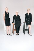 full length view of fashionable three-generation blonde women in total black outfits near chairs isolated on grey