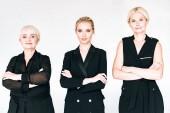 modische drei Generationen blonde Frauen in total schwarzen Outfits mit gekreuzten Armen isoliert auf grau