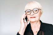 senior businesswoman in black outfit and glasses talking on smartphone isolated on grey