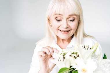 exited blonde senior woman in white clothes with flowers isolated on grey