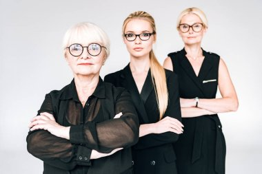 fashionable three-generation blonde businesswomen in glasses with crossed arms isolated on grey