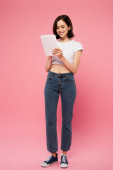 Fotografie full length view of beautiful smiling girl using digital tablet isolated on pink