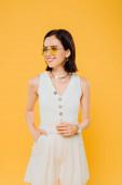 Fotografie elegantní žena v brýlích s úsměvem izolovaná na žluté