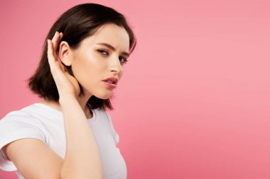 beautiful focused girl listening isolated on pink
