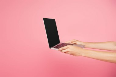 Partial view of girl holding laptop with blank screen isolated on pink stock vector