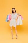 boldog nő napszemüveg gazdaságban bevásárló táskák izolált sárga