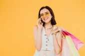 Photo happy fashionable girl in sunglasses with shopping bags talking on smartphone isolated on yellow