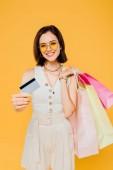boldog lány napszemüveg bevásárló táskák bemutató hitelkártya izolált sárga